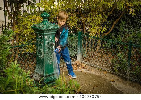 Boy washes his toy at a decorative water fountain in Paris