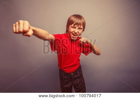 European-looking boy of ten years shows a fist, anger, danger, mouth open on a gray background retro poster