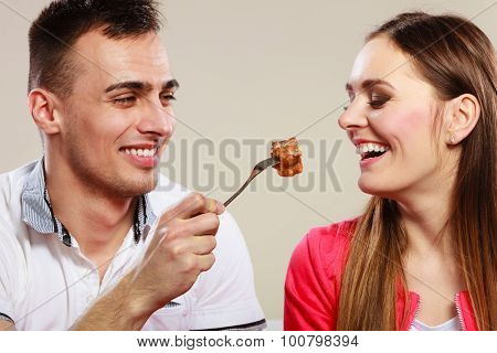 Smiling Man Feeding Happy Woman With Cake.