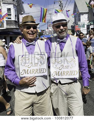 Just married gay couple walking Provincetown Carnival Parade in Provincetown, Massachusetts.