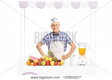 Mature soda jerk in white apron standing behind a stand full of fresh fruits isolated on white background