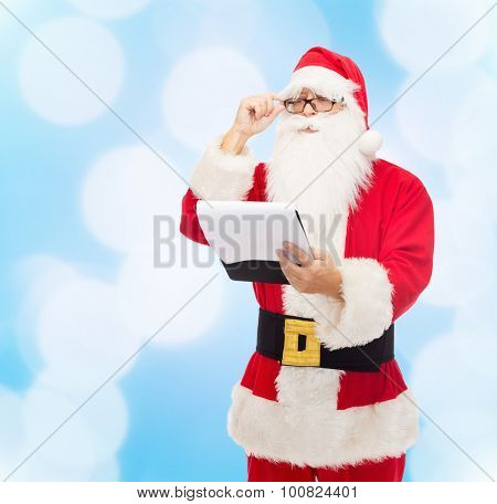 christmas, holidays and people concept - man in costume of santa claus with notepad over blue lights background