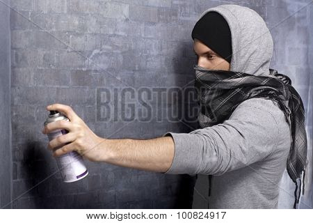 Graffiti man in hooded shirt and face mask spraying brick wall by aerosol can.