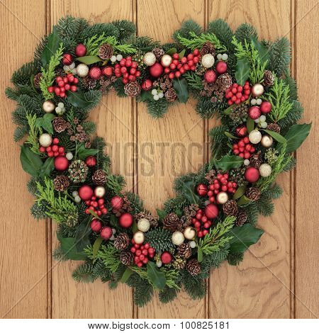 Christmas heart shaped wreath with red bauble decorations, holly, mistletoe and greenery over oak  front door background. poster