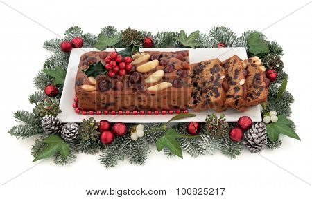 Genoa cake with holly, mistletoe, christmas red bauble decorations and winter greenery over white background. poster