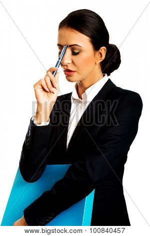 Pensive businesswoman holding a pen and binder.