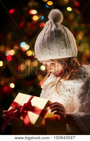 Little girl in white winterwear holding open giftbox