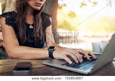 Woman Working On Laptop At An Outdoor Cafe