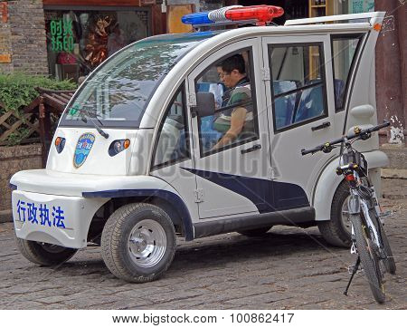 police officer is sitting inside the car in Lijiang, China