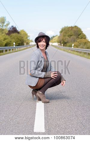 Jaunty Trendy Young Woman Crouching On A Road