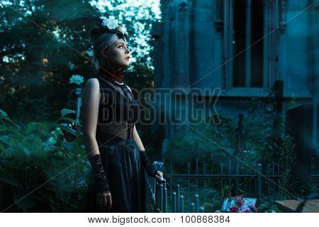 Woman Stands In A Cemetery At Night.