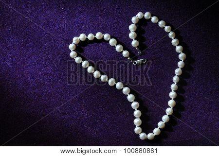 pearl beads in heart shape on purple velvet background