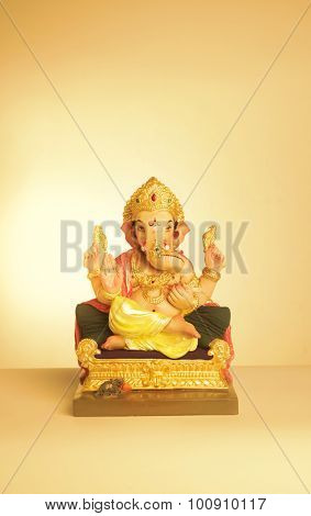 Statue of colorful Ganesha idol on yellow background. Greeting card cover template.