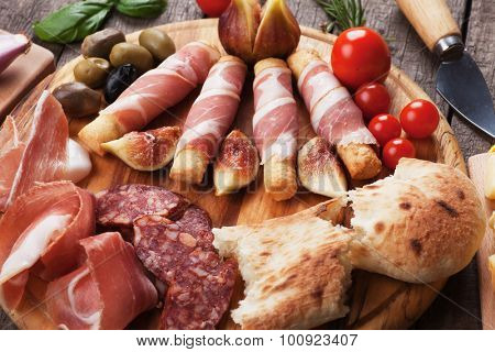 Prosciutto di Parma and other italian food on wooden table
