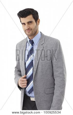 Portrait of goodlooking young elegant businessman, looking at camera, smiling.