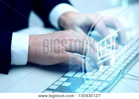 business, technology, online commerce and internet concept - close up of businessman hands typing on keyboard with shopping trolley hologram