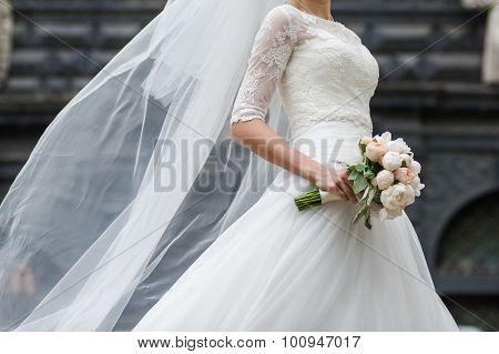 Bride, row of bridesmaids with bouquets at big wedding ceremony.