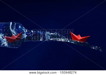 Red Paper Boats Escape On A Water Splash From A Bottle, Dark Blue Background