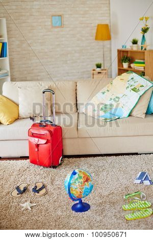 Sofa with map, pillow and globe, airline tickets, flipflops and suitcase near by