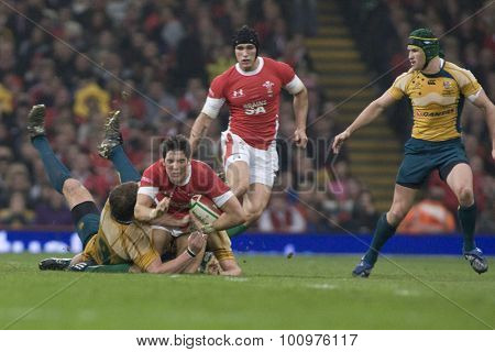 CARDIFF, WALES. 28 NOVEMBER 2009. James Hook of Wales is tackled  while playing in the Invesco Perpetual International Rugby Union match between Wales and Australia at the Millennium Stadium.