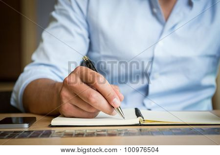 Closeup shot of a man taking down note in a personal organizer. Young man's hand writing in diary. Close up of hand of a businessman writing on a business plan.