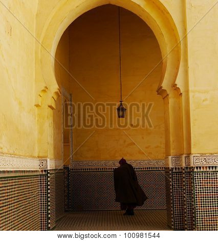A mysterious cloaked figure seen through an archway within the Mausoleum of Moulay Ismail decorated with traditional tiles and yellow walls in the Moroccan city of Meknes