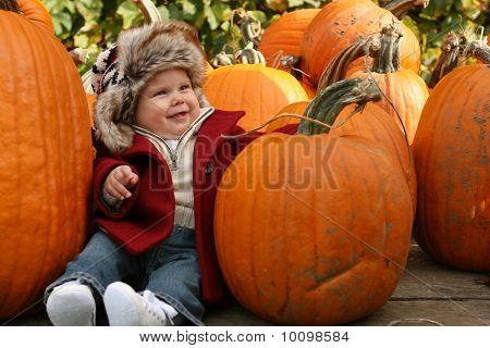 Little baby amongst pumpkins