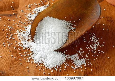 Coarse grained salt on a wooden scoop