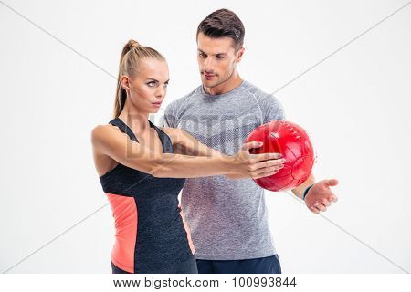 Portrait of a beautiful woman workout with fitness ball with trainer isolated on a white background