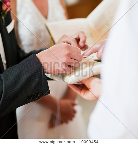 Groom taking rings in wedding ceremony