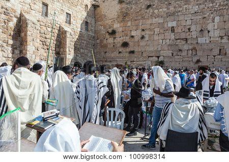 JERUSALEM, ISRAEL - OCTOBER 12, 2014:  Huge crowd of faithful Jews wearing white prayer shawls and black long-skirted coats. Morning Sukkot