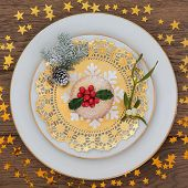 Mince pie and holly with mistletoe, snowflake  and winter greenery over oak background with gold stars. poster
