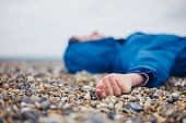 An unconscious woman is lying on a shingle beach poster