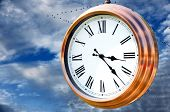 Time for migration concept: Copper clock face over beautiful cloudy sky with geese in V shape flight formation in the background. poster