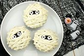 Group of Halloween mummy cupcakes on white plate with candies on black cloth background poster