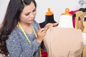 A porttrait of a fashion designer or Tailor working on a design or draft fix it with sewing needle poster