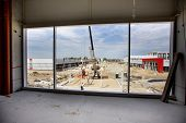 Building site atmosphere seen through large window of building under construction poster