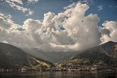 Mountain peaks puffy clouds and Zeller lake views from Zell am See Austria poster