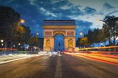 Image of the iconic Arc de Triomphe in Paris city during twilight blue hour. poster