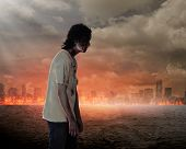 Creepy male zombie in the city that on fire poster