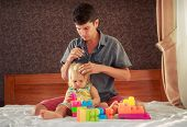 little blonde girl in colourful dress plays toy constructor and father brushes her hair on sofa poster