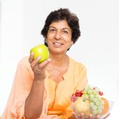 Old people healthy eating. Portrait of a 50s Indian mature woman eating fruits at home. Indoor senior people living lifestyle. poster