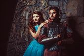 Medieval knight with his beloved lady on the ancient castle background. poster