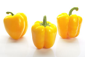 Three yellow peppers on the white background