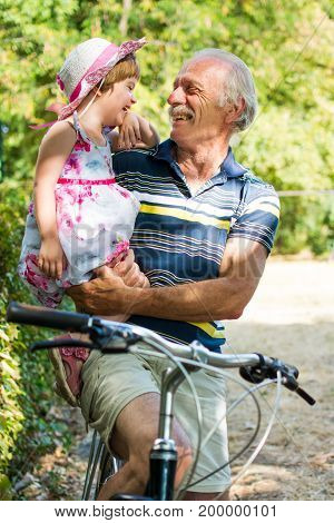 Grandpa Laughing On Bicycle With Granddaughter