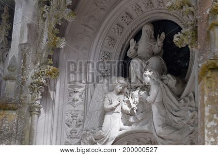 Detail in the park - old stone statue with angels, Quinta da Regaleira Sintra, Portugal.