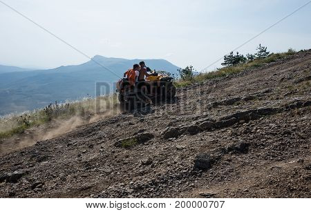 Three young guys are driving an ATV up a mountain road