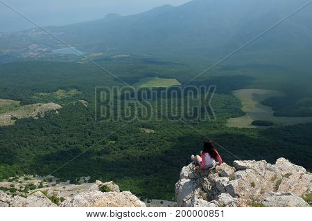 A young girl sits on edge cliff and looking at mountain landscape