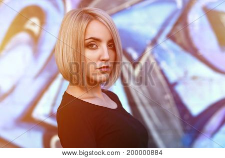 Portrait Of A Young Blond Girl With Short Hair On A Background Of A Painted Wall