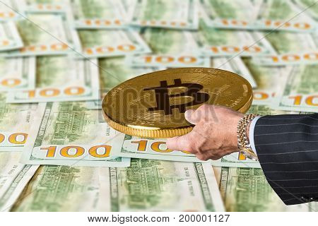 Businessman hand holding a bitcoin over a table full of US one hundred dollar bills. This shows the value or exchange rate of the virtual currency